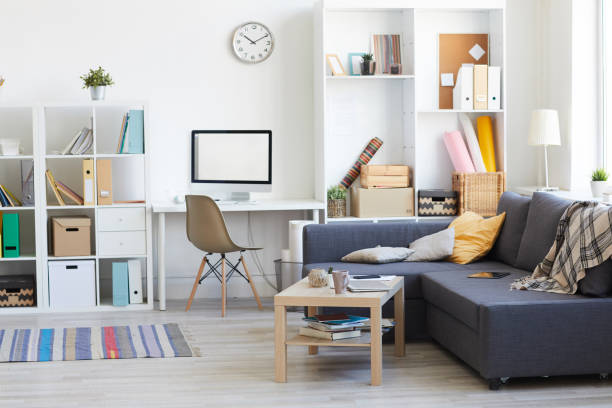 Male Apartment Interior Wide angle shot on domestic interion in white and blue with home workplace in living room, copy space bachelor stock pictures, royalty-free photos & images