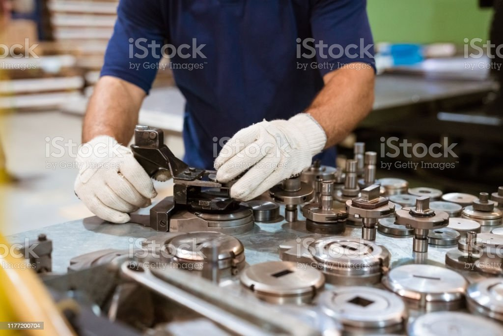 Male apprentice using manufacturing machinery Midsection of male apprentice using manufacturing machinery. Young engineer is working in factory. He is wearing protective gloves. 20-24 Years Stock Photo