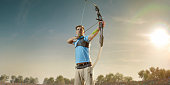 Male archer shooting with the longbow at sunset. Archer in professional field with a lot of fans.