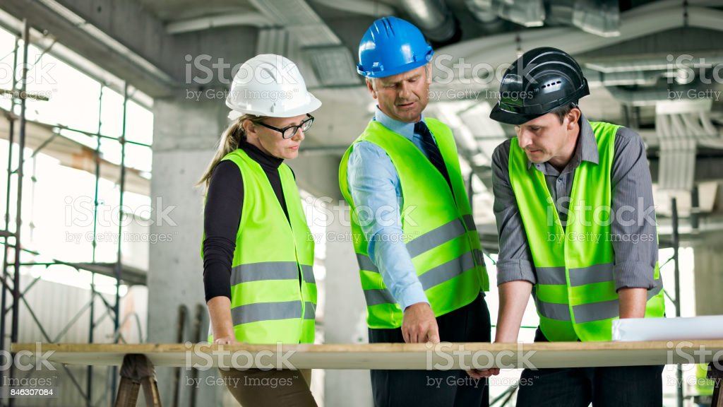 Male architect and female construction coordinator talking to investor on the site of construction stock photo