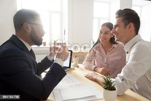 Male architect or interior designer gesturing discussing house project with excited millennial couple, realtor talking with young spouses about mortgage loan or purchase, consulting about offers