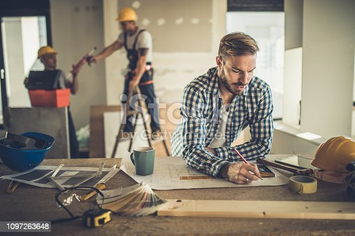 891274328 istock photo Male architect drawing improvements on housing plan at construction site. 1097263648