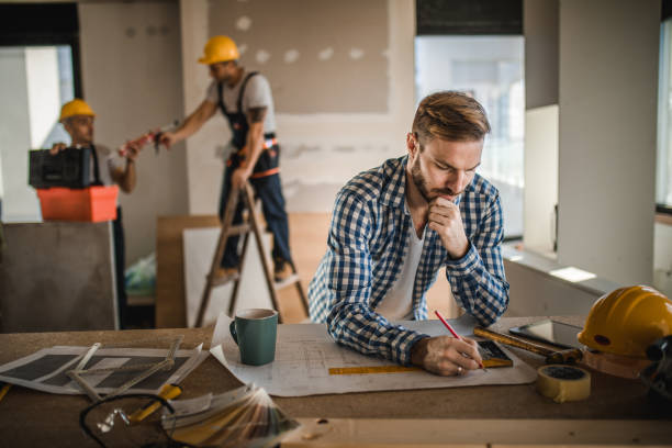 Male architect drawing improvements on housing plan at construction site. stock photo