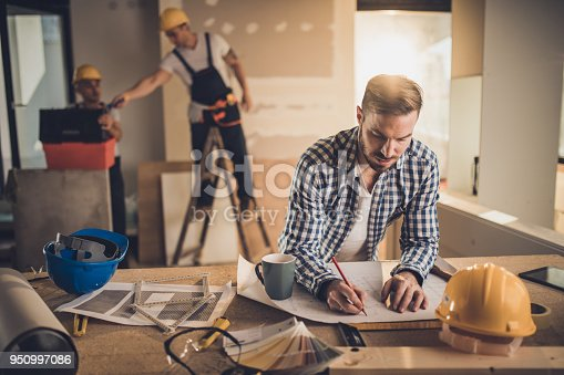 891274328 istock photo Male architect drawing improvements on housing plan at construction site. 950997086