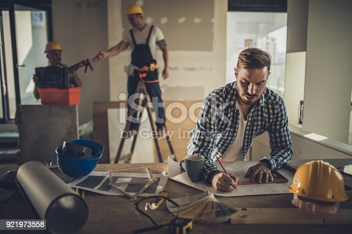 891274328 istock photo Male architect drawing improvements on housing project inside of a built structure. 921973558