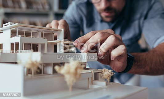 istock Male architect hands making model house 823322674