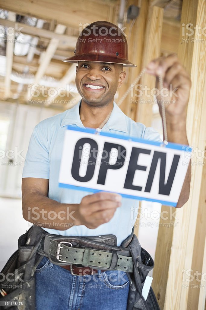Male Architect Holding Open Sign At Construction Site royalty-free stock photo