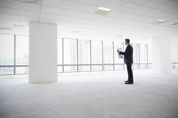 Male Architect In Modern Empty Office Looking At Plans stock photo