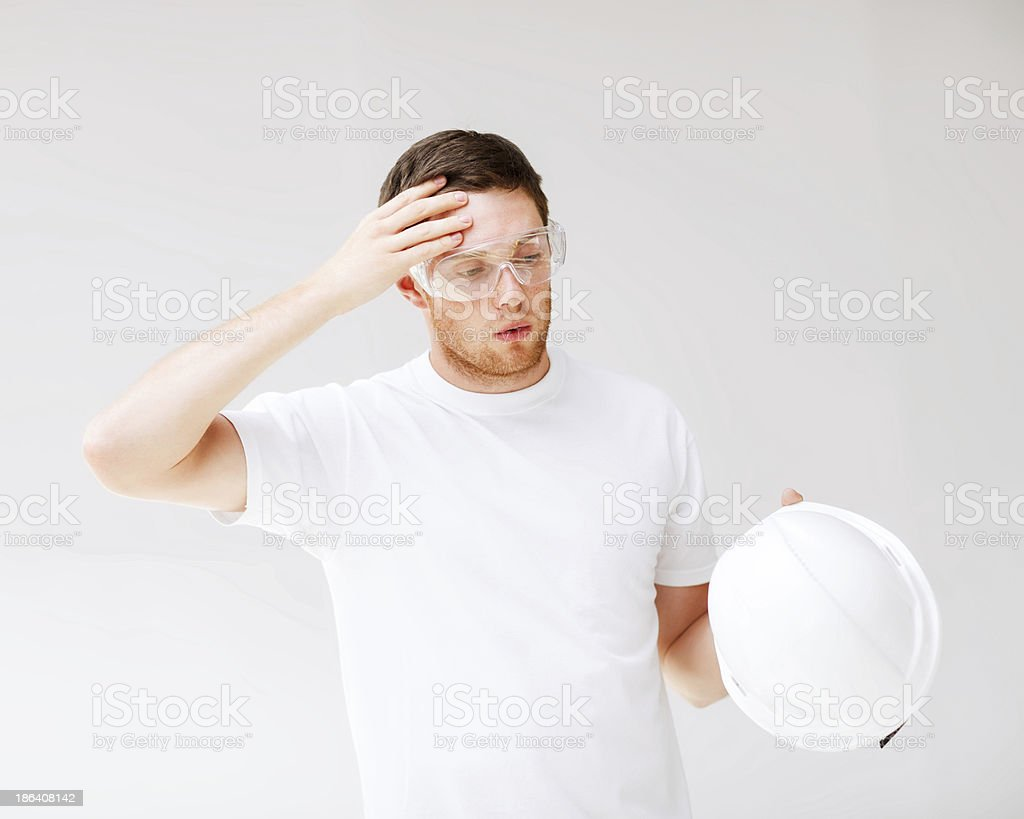 male architect in safety glasses taking off helmet royalty-free stock photo