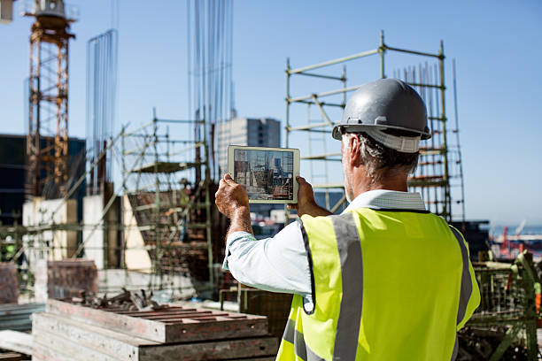 male architect photographing construction site - construction industry stock pictures, royalty-free photos & images