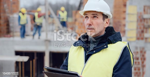 Male architect holding digital tablet and checking plans while standing in middle of construction site.