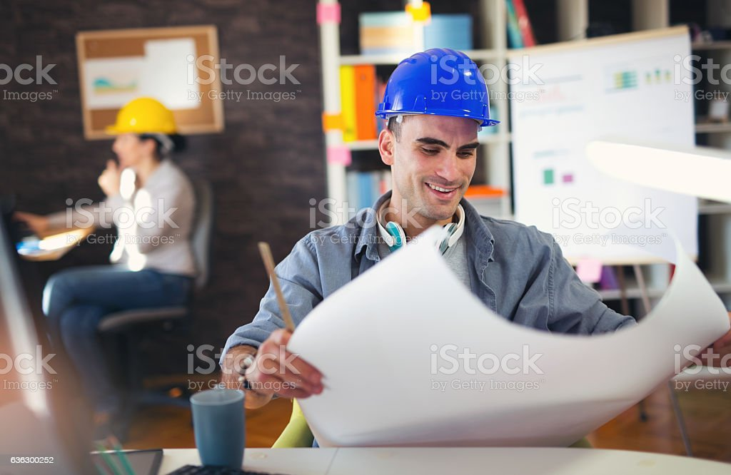 Male architect studying plan in office - foto de stock