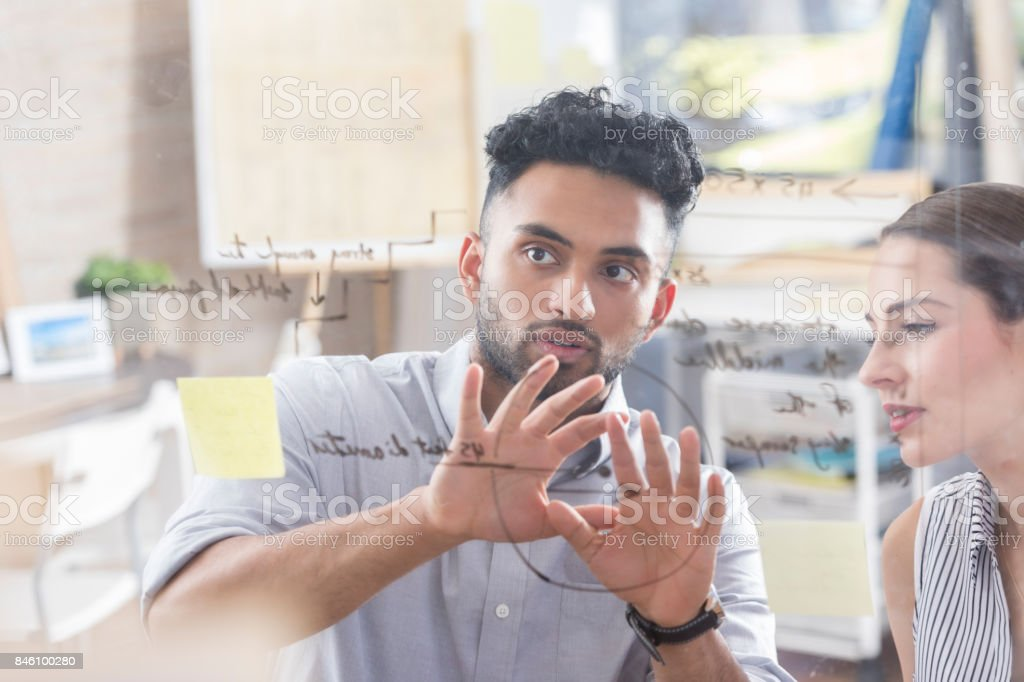 Male architect talks with colleague about blueprint stock photo