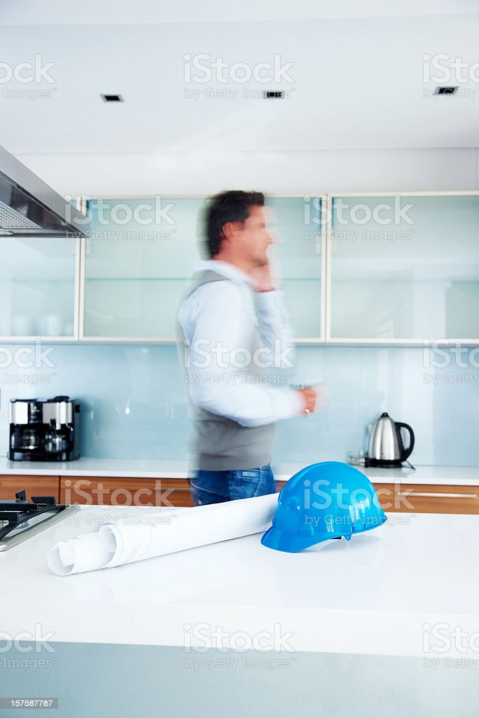 Male architect using phone with blueprints on table royalty-free stock photo