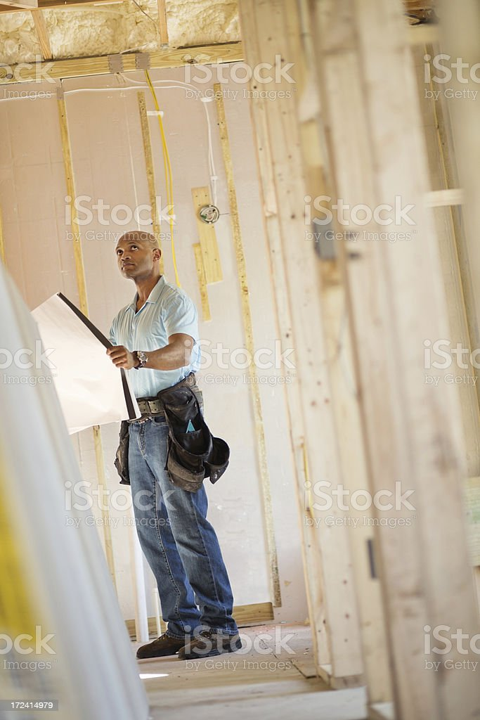 Male Architect With Blueprint Analyzing Construction Site royalty-free stock photo