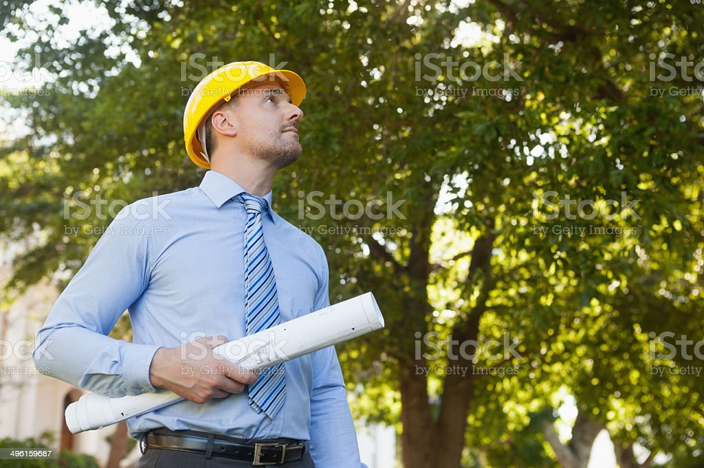 Low angle view of a young male architect with blueprint standing...