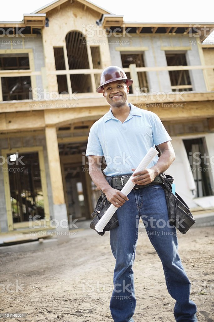 Male Architect With Blueprint Standing In Front Of Incomplete Ho royalty-free stock photo
