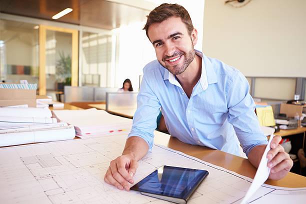 männliche architekt studium pläne mit tablet pc im büro - architekturberuf stock-fotos und bilder