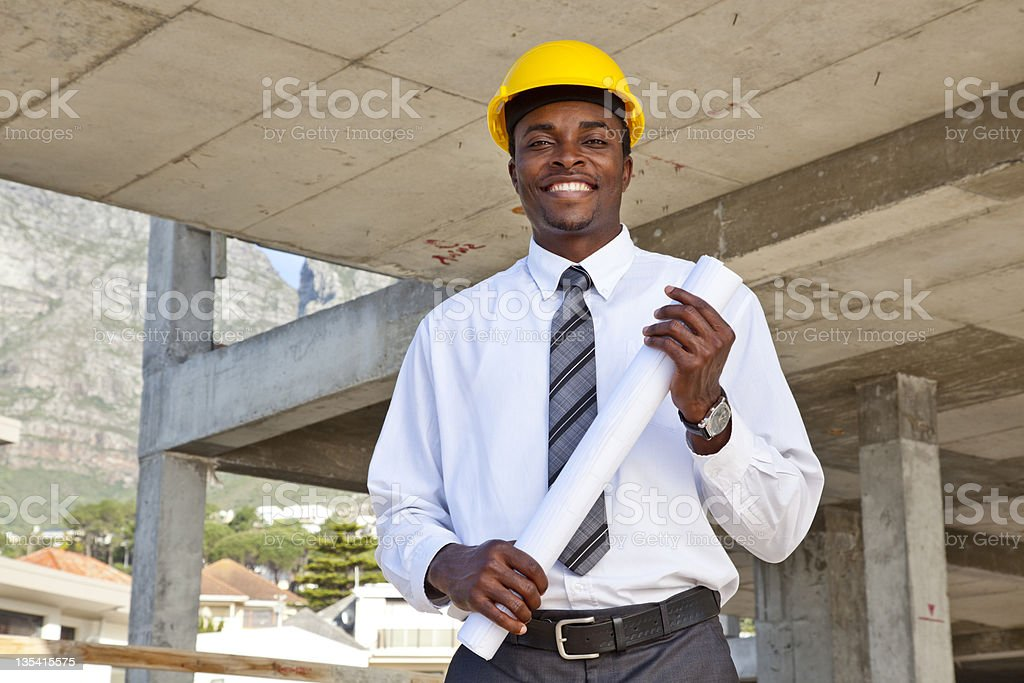 Male architect with hard hat holding blueprints stock photo