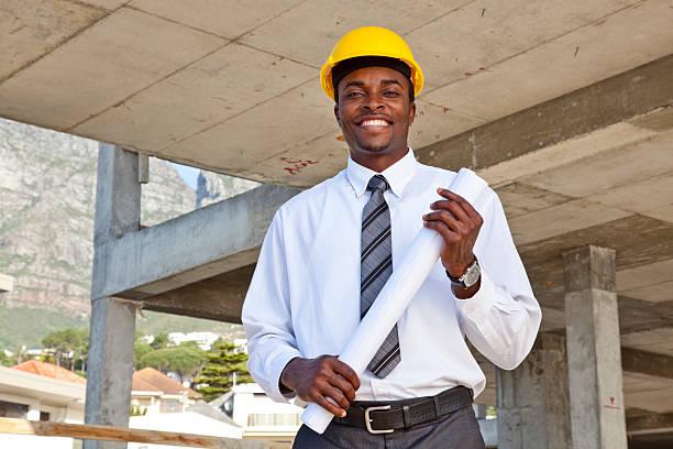 Male architect with hard hat holding blueprints stock photo