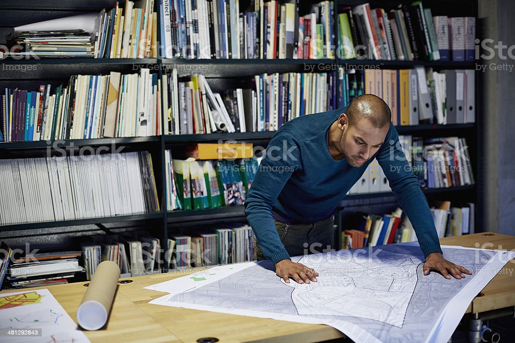 Male architect working on project by workstation in modern office
