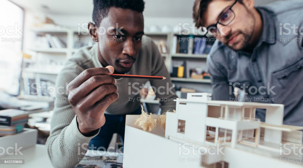Male architects in office discussing construction project stock photo