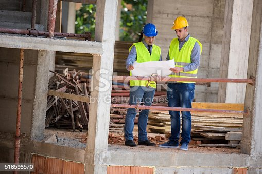516607254 istock photo Male architects look at blue print on building construction 516596570