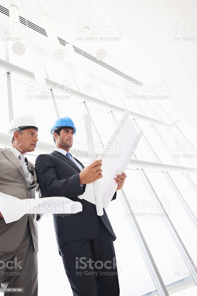 Male architects with blue prints in hand royalty-free stock photo