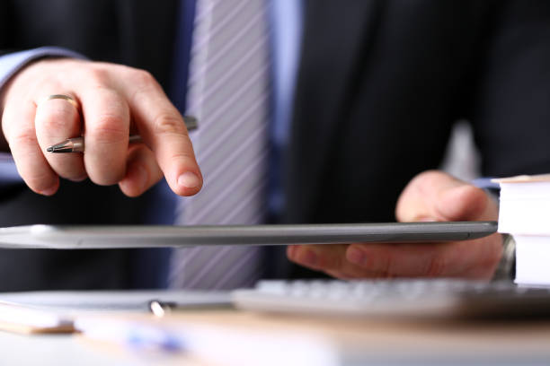 Male arm in suit and tie use silver pen and tablet pc stock photo