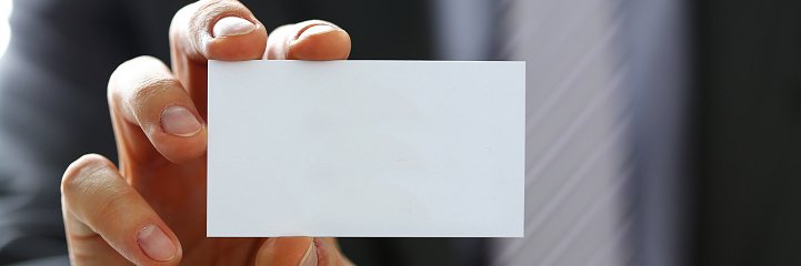istock Male arm in suit give blank calling card to visitor 846719548