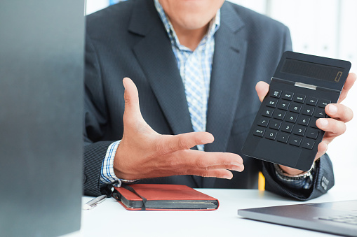1018458132 istock photo Male arm in suit hold calculator showing calculator in office closeup. Outraged boss shows on the calculator the difference between debit and credit 1018089732