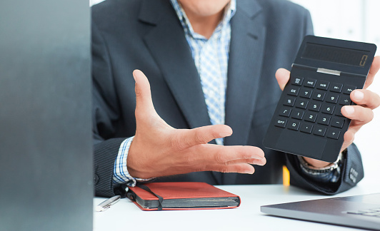 1018458132 istock photo Male arm in suit hold calculator showing calculator in office closeup. Outraged boss shows on the calculator the difference between debit and credit 1021548530
