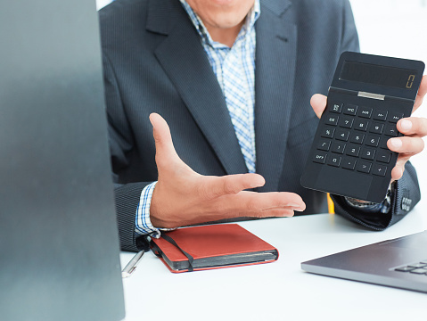 1018458132 istock photo Male arm in suit hold calculator showing calculator in office closeup. Outraged boss shows on the calculator the difference between debit and credit 1021599786