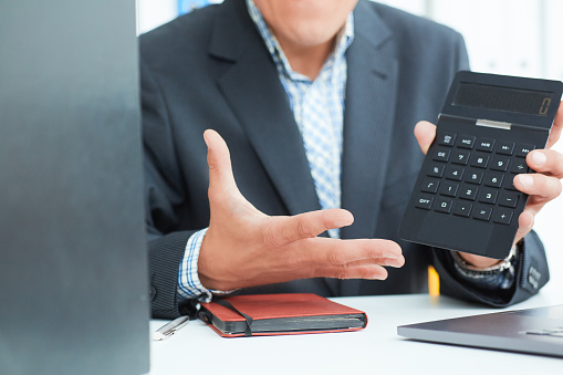 1018458132 istock photo Male arm in suit hold calculator showing calculator in office closeup. Outraged boss shows on the calculator the difference between debit and credit 1021599820