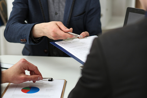 863148614 istock photo Male arm in suit offer contract form on clipboard pad 801300232