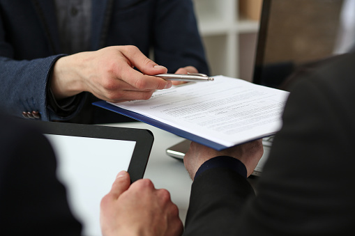 863148614 istock photo Male arm in suit offer contract form on clipboard pad 801300244