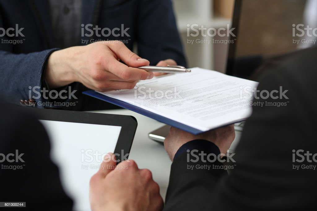 Male arm in suit offer contract form on clipboard pad stock photo