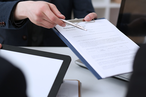 863148614 istock photo Male arm in suit offer contract form on clipboard pad 808396106