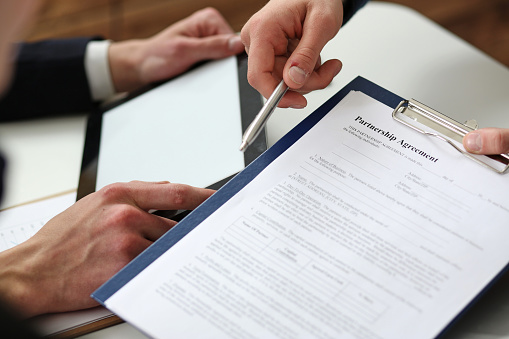 863148614 istock photo Male arm in suit offer contract form on clipboard pad 825439806