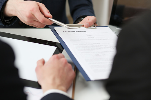 863148614 istock photo Male arm in suit offer contract form on clipboard pad 841152714