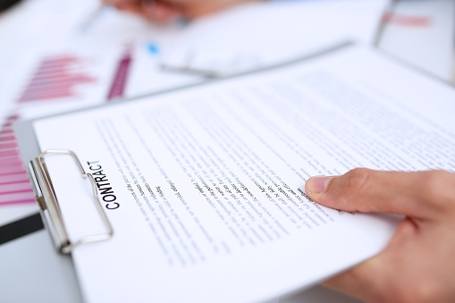 863148614 istock photo Male arm in suit offer contract form on clipboard pad 863152874
