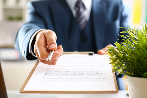 863148614 istock photo Male arm in suit offer contract form on clipboard 876838138
