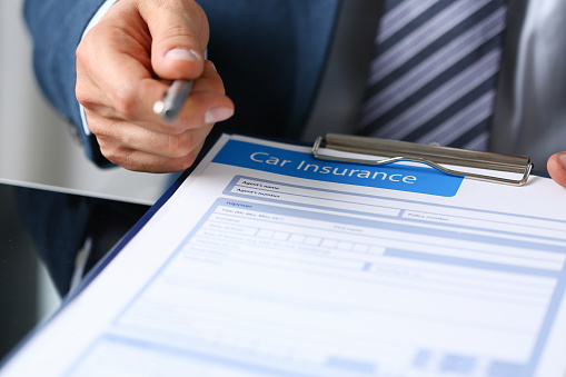 istock Male arm in suit offer insurance form clipped 1127314083