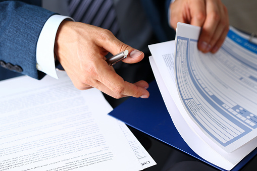 istock Male arm in suit offer insurance form clipped to pad 857794116