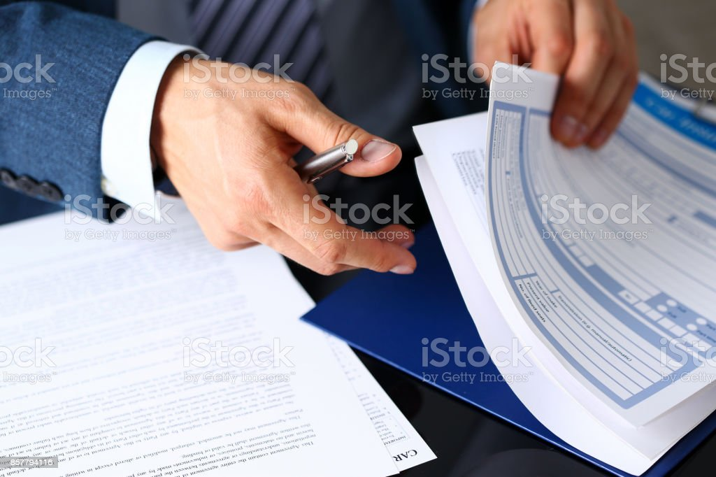 Male arm in suit offer insurance form clipped to pad stock photo