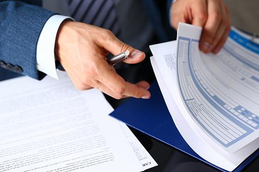Male Arm In Suit Offer Insurance Form Clipped To Pad - Fotografie stock e altre immagini di Abbigliamento formale