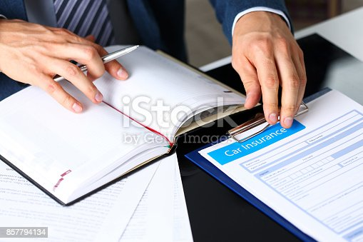 863128060 istock photo Male arm in suit offer insurance form clipped to pad 857794134