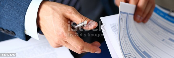 istock Male arm in suit offer insurance form clipped to pad 863128060