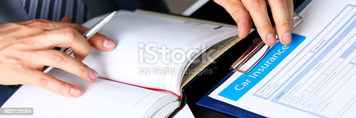 863128060istockphoto Male arm in suit offer insurance form clipped to pad 863128064
