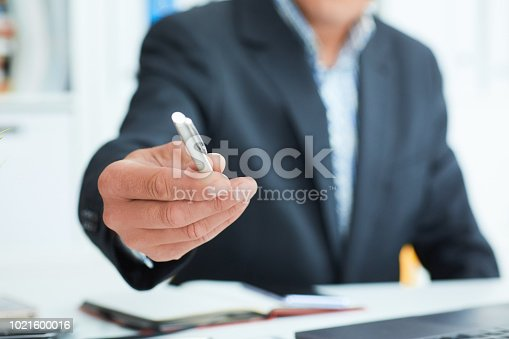 Middle section of businessman in suit offer silver pen to sign contract closeup. Strike a bargain for profit, white collar motivation, union decision, corporate sale, insurance agent concept